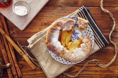 Handmade apple pie. On a dish over a napkin in a country style, cinnamon and hony in the background Royalty Free Stock Image