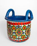 Handmade artistic pained colorful decorated pottery basket with two handles. On white background Stock Photo