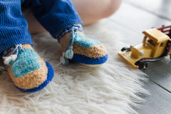 Handmade baby booties. Baby booties on the child dressed royalty free stock photography