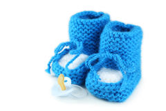 Handmade baby booties with pacifier isolated on a white Royalty Free Stock Photography