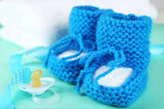 Handmade baby booties with pacifier on the mint background Stock Photo
