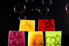 Handmade backlit soap. Color handmade backlit soap and soap bubbles over black stock photo
