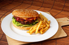 Handmade Bacon Cheeseburger. Bacon cheeseburger with a homemade beef patty on a bed of lettuce with a side of fries Stock Photos