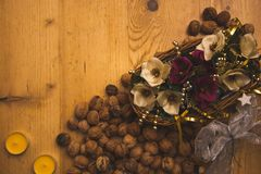 The handmade basket with beautiful artifical blooms and handful of nuts royalty free stock images