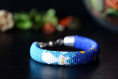 Handmade beaded blacelet with white cat and moon. On a dark background Stock Images