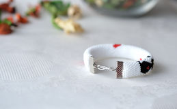 Handmade beaded bracelet with the image of a black cat and red hearts Stock Photography