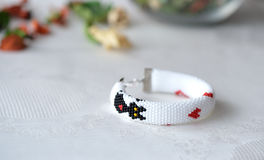 Handmade beaded bracelet with the image of a black cat and red hearts Stock Photos