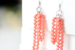 Handmade beaded earrings coral color. Close up Stock Images