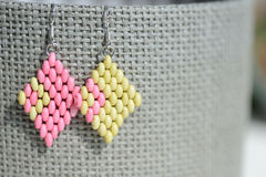 Handmade beaded earrings light green and pink color. Close up Stock Photo