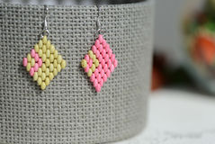 Handmade beaded earrings light green and pink color. Close up Royalty Free Stock Photos