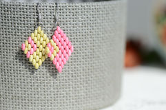 Handmade beaded earrings light green and pink color. Close up Royalty Free Stock Images
