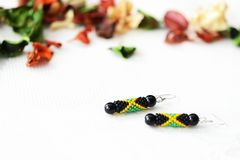 Handmade beaded earrings in style of jamaican flag. Close up stock images