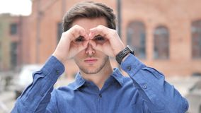 Handmade Binocular Gesture by Handsome Young Man Searching New Chance. 4k high quality, 4k high quality stock footage