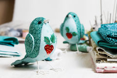 Handmade bird sewed from a cloth stands on a white wooden table Royalty Free Stock Photo