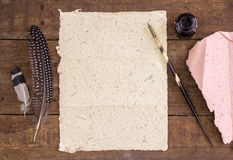 Handmade blank paper, quill pen and ink or rustic wood desk Royalty Free Stock Photos