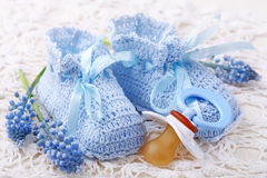 Handmade blue baby booties. With dummy and flowers royalty free stock images