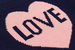 Handmade blue knitted fabric with pink heart and word Love bound on knitting needles as backgroun or texture royalty free stock image