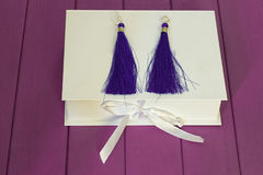 Handmade blue threaded earrings. And a white box on a purple wooden background Royalty Free Stock Image