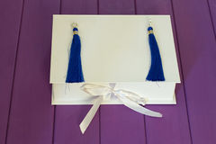 Handmade blue threaded earrings. And a white box on a purple wooden background Stock Photography