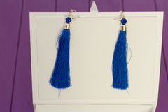 Handmade blue threaded earrings. And a white box on a purple wooden background Royalty Free Stock Photography