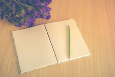 Handmade book with pencil and Statice flower on wooden table Royalty Free Stock Images