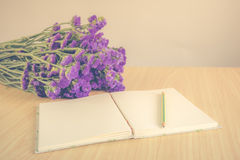 Handmade book with pencil and Statice flower on wooden table Stock Images