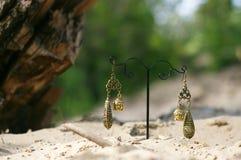 handmade Boucles d'oreille sur le support avec des buddhas sur le sable Images libres de droits