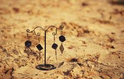 handmade Boucles d'oreille sur le support sur le sable Photo stock