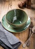 Handmade bowl and plate of green color with vintage spoon and fork on wooden background. stock photo