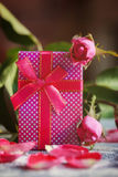 Handmade box with gift  on old pink roses background. Stock Photos