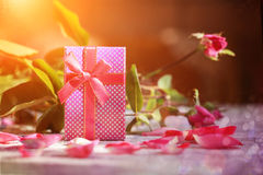 Handmade box with gift  on old pink roses background Stock Image