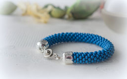 Handmade bracelet of blue beads on textile background Stock Photography