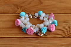 Handmade bracelet with flowers made of polymer clay, plastic beads and metal pendants Stock Photos
