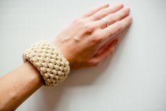 Handmade bracelet, light yellow threads, a hand with a ring. Handmade bracelet, grey and yellow threads, a hand with a ring royalty free stock image