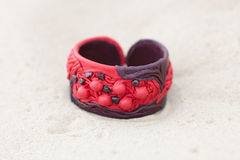 Handmade bracelet with leather on sand.  Royalty Free Stock Image