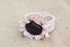Handmade bracelet with leather on sand.  Stock Photo