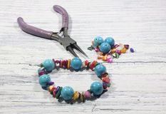 Handmade bracelet with semi-precious natural stones, a tool for handmade and stone beads on a light background. royalty free stock photos