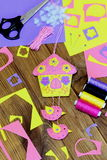 Handmade bright house with flowers and birds made of felt. Beautiful wall decoration, sewing materials and tools on wooden table Royalty Free Stock Photography