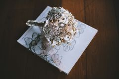Handmade brooch bouquet on the white book on wooden floor stock photography