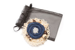 Handmade brooch having shape of the flower made from denim on white lace fabric Stock Image