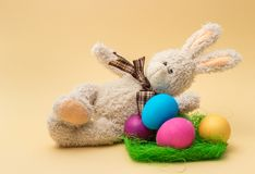 Handmade Bunny and Easter Colored Eggs. Beige background. stock photos