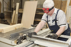 Handmade business at small furniture factory. Worker using saw machine to make furniture at carpenters workshop. Handmade business at small furniture factory Royalty Free Stock Image