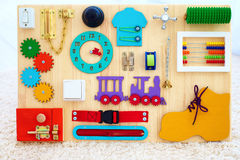 Handmade busy board for baby fine motility skills development Royalty Free Stock Photo