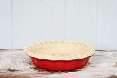 Handmade Butter Pie Crust in Pie Plate. Homemade butter pie crust in pie plate with fluted pinched edge against a rustic wooden background. Crust is empty and stock photo