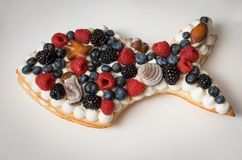 Handmade cake in the form of fish. Puff cake with cream decorated with sea theme. Cake decorated with raspberries, blueberries, blackberries, and chocolates stock photos