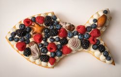 Handmade cake in the form of fish. Puff cake with cream decorated with sea theme. Cake decorated with raspberries, blueberries, blackberries, and chocolates stock photography