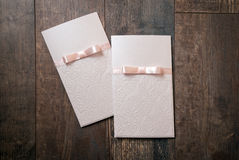 Handmade card with embossed details and pink bow on wood backgro Stock Photography