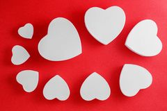 Handmade cardboard hearts on a red background. The concept is suitable for love stories and for Valentine`s Day.  stock photo