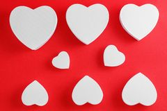 Handmade cardboard hearts on a red background. The concept is suitable for love stories and for Valentine`s Day.  stock photography