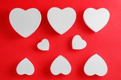 Handmade cardboard hearts on a red background. The concept is suitable for love stories and for Valentine`s Day.  stock images